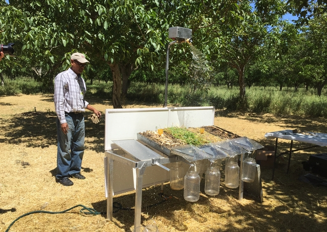 NRCS Regional Soil Health Coordinator Kabir Zahangir demonstrates differences in soil from no-till management under rainfall simulator.
