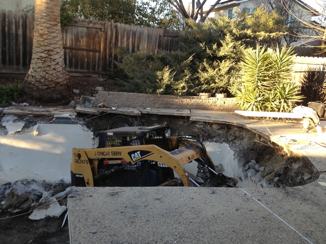 Bobcat tearing out the backyard pool