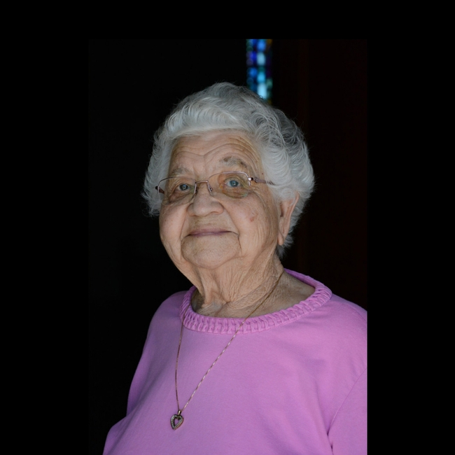 Gray haired older woman in pink top on black background