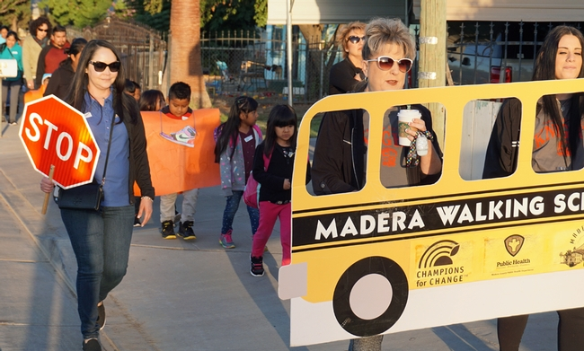 UC CalFresh manager Karina Macias, left, leads the Virginia Lee students along with teachers Carolyn Lozano and Aubrey Rutherford (left to right, holding the school bus banner.)