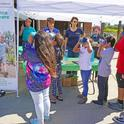 Children peer through VR goggles to see an undersea world, a 4-H activity shared with potential new members at the harvest festival. Behind the table from left are 4-H volunteer Stan Alger, 4-H program representative Sue Weaver, 4-H youth development advisor Fe Moncloa, and 4-H teen ambassador Alexa Russo.