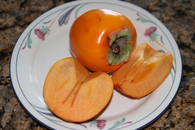 Image of Fuyu persimmon fruit slices on a plate.