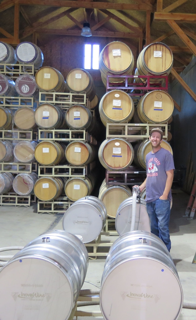 A man with a hose and barrels in a winery.