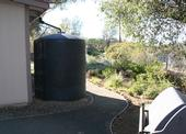A foothill dwelling landscaped with a five-foot non-combustible zone. The building is also equipped with an extra large rain barrell that collects water during storms for irrigating plants.