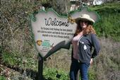 UC ANR Master Gardener coordinator Kris Randal with the welcome sign on the Mariposa Creek Parkway.