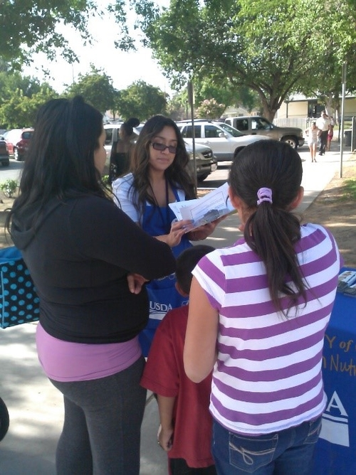 Consuelo Cid teaches a family at Burroughs Elementary about a Healthy Plate.