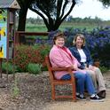 Debra Jamison (left), state regent, and Gayle Mooney, state treasurer, share a bench that the California State Society of the Daughters of the American Revolution purchased for the UC Davis bee garden.