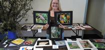 Dixon May Fair Youth Building superintendent Sharon Payne with some of the insect photographs taken by youth exhibitors. (Photo by Kathy Keatley Garvey) for Bug Squad Blog