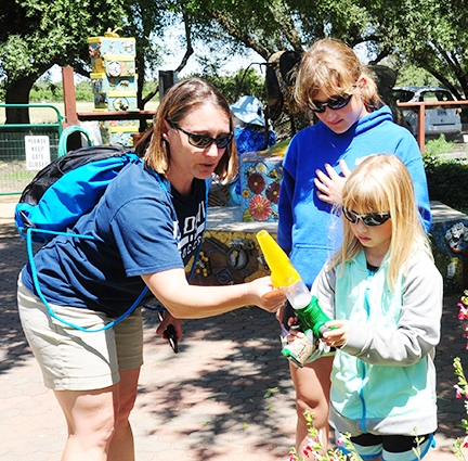 UC Davis Athletics employee Nicole Morrill admires a bee caught by her daughter, Samantha, 8, as sister Hannah, 11, watches.