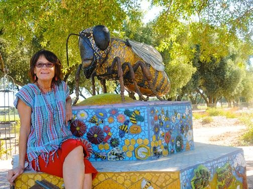 Artist Donna Billick of Davis with her ceramic and mosaic sculpture of a six-foot-long worker bee, Miss Bee Haven. The sculpture anchors the garden.