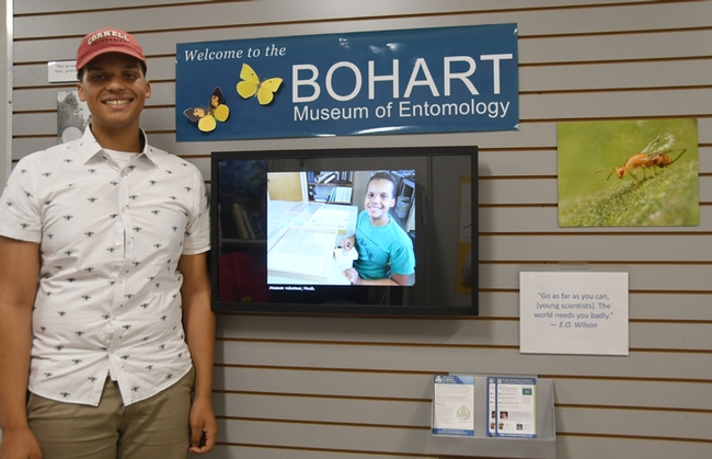 Noah Crockette stands by a wall-mounted computer screen with an image of him at age 14. (Photo by Kathy Keatley Garvey)