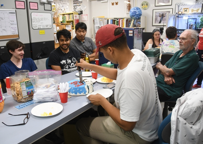 Bohart associates watch while Noah Crockette cuts the cake. At left are students Parras McGrath, Lohit Garikipati, and Minsu Kang. At right is Robbin Thorp, UC Davis distinguished emeritus professor of entomology. (Photo by Kathy Keatley Garvey)