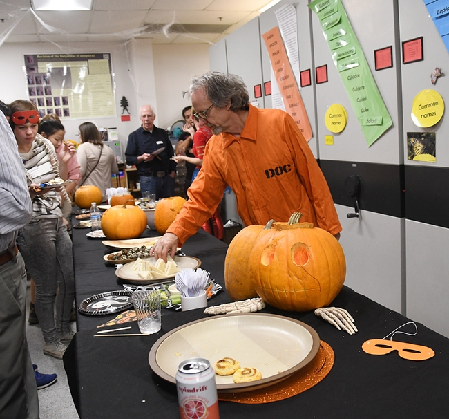 Senior museum scientist Steve Heydon dressed in an orange jumpsuit, lettered in back