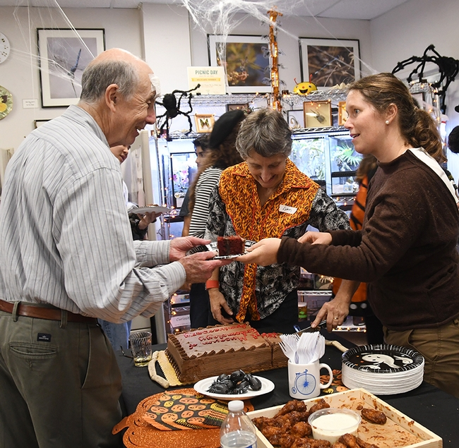 Lynn Kimsey (center), Bohart Museum director, and Tabatha Yang, education and outreach coordinator, serve cake to Bruce Hammock, distinguished professor of entomology who holds a joint appointment with the UC Davis Comprehensive Cancer Center. (Photo by Kathy Keatley Garvey)