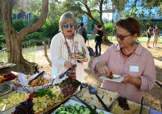 Amina Harris (right), director of the UC Davis Honey and Pollination Center, chats with honey bee veterinarian Terry Ryan Kane of Ann Arbor, Mich., at the Thursday night reception. The Honey and Pollination Center organized the conference. (Photo by Kathy Keatley Garvey)