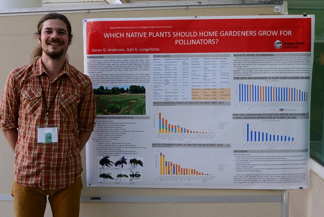 Researcher Aaron Anderson of Oregon State University stands by his poster on