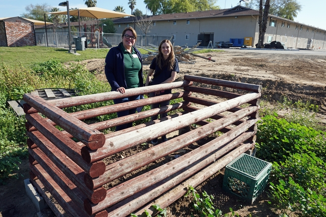 UC CalFresh nutrition educators Nancy Zumkeller, left, and Kristi Sharp stand at the compost bin at Rescue the Children. The residents are learning to compost food scraps, garden trimmings, hair from their brushes, lint from dryers and paper.