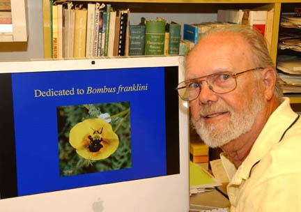 Bumble bee expert Robbin Thorp with a photo he took of Franklin's bumble bee. (Photo by Kathy Keatley Garvey)