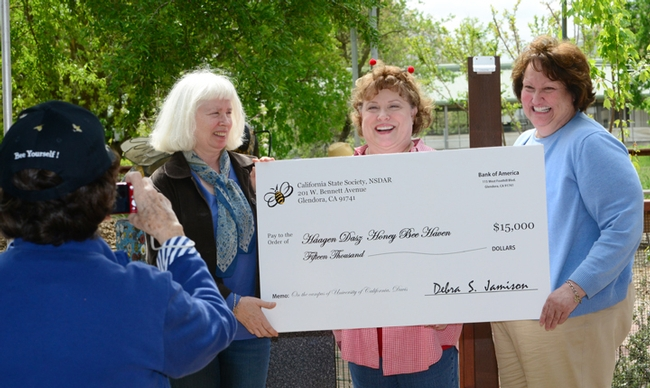 A member of the California State Society of the Daughters of the American Revolution photographs the check presentation. From left are Chris Casey, manager of the haven; Debra Jamison, State Regent of DAR; and Karen Montgomery, the state project chair. (Photo by Kathy Keatley Garvey)