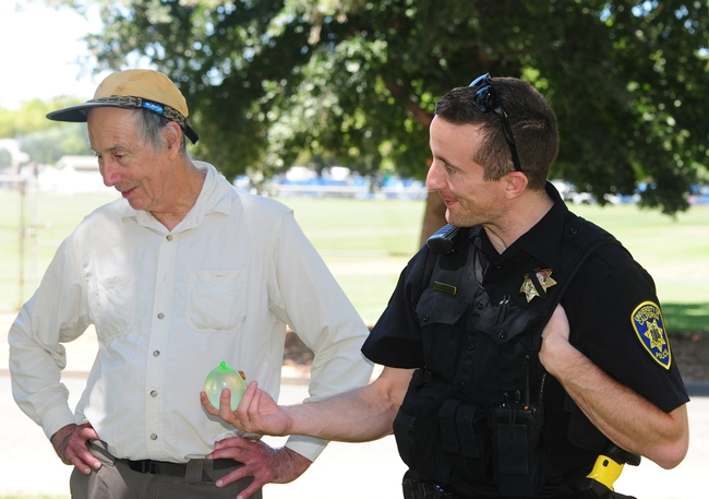 Bruce Hammock ponders tips on water balloon battling as he chats with UC Davis police officer Stephen Jerguson, who was handed a water balloon  for