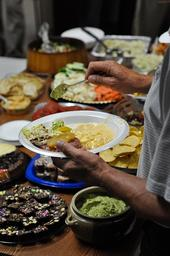 A person's hand putting food on their plate at a potluck.