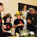 "The 4-Alarm Chili Team of the Dixon Ridge 4-H Club and the newly formed Pleasants Valley 4-H Club, watches as judge John Vasquez Jr. samples their dish.  From left are Randy Marley, ""captain"" Cody Ceremony and ""driver"" Justin Means. In back (at right) is Justin's uncle, Chuck Means, who provided the recipe and the firefighter uniforms. Chuck Means is an engineer with Sacramento Metropolitan Fire District and a co-community leader of the Dixon Ridge 4-H Club. (Photo by Kathy Keatley Garvey)"