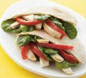 Chicken pita pocket with spinach leaves and red bell pepper.