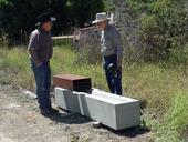UC Cooperative Extension rangeland farm advisor Royce Larsen, left, discusses the ground-level water trough with inventor George Work.