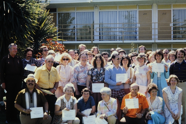 A group of freshly graduated UC Master Gardener volunteers in three rows holding up their certificates of completion.