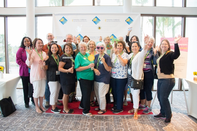 UC Master Gardener volunteers in front of a step and repeat, posing for a photograph with their hands in the air.
