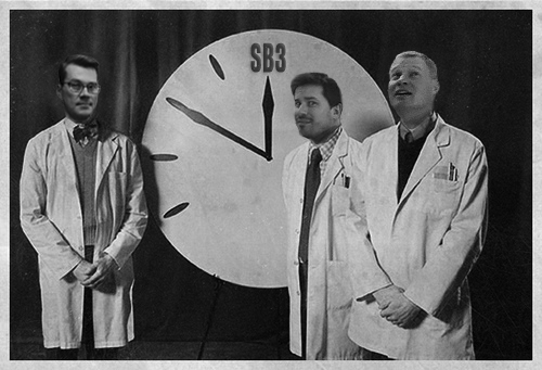 Image of Alex, Karl and Dave standing near a clock pointing to Site Builder 3