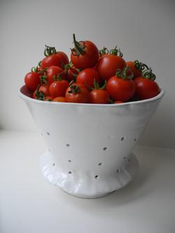 The plentiful harvest is displayed in a hand thrown colander from Peru, home of wild ancestor tomatoes. Photo: Anne-Marie Walker