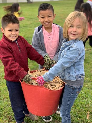 Kids hauling wood chips for the garden. Photo CalFresh Healthy Living, UC