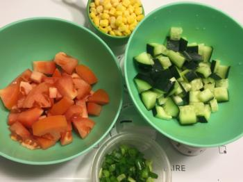 Prepare toppings while pasta cooks: 1 small tomato (diced), 1/2 cucumber (diced), 1/2 cup corn, 2 green onions (chopped)