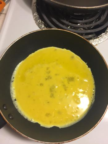 Pour eggs evenly into the pan.