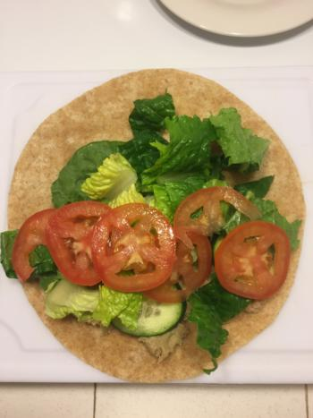 Tuna on whole wheat tortilla topped with cucumbers, lettuce, and tomatoes