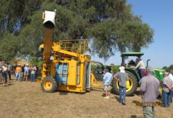 A group of farmers looking at a stationary mechanical grape harvester