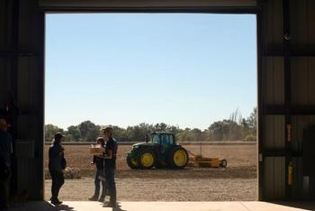 Researchers talk while a tractor moves across a field at the UC Davis Russell Ranch Sustainable Agriculture Facility in 2016