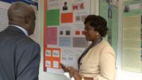 Dr. Ngozi Abu discussing her research poster with guest.