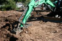 Excavator loosening the soil