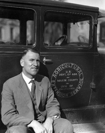 M.B. Boissevain sitting on the sideboard of the Extension Service Ford Model T