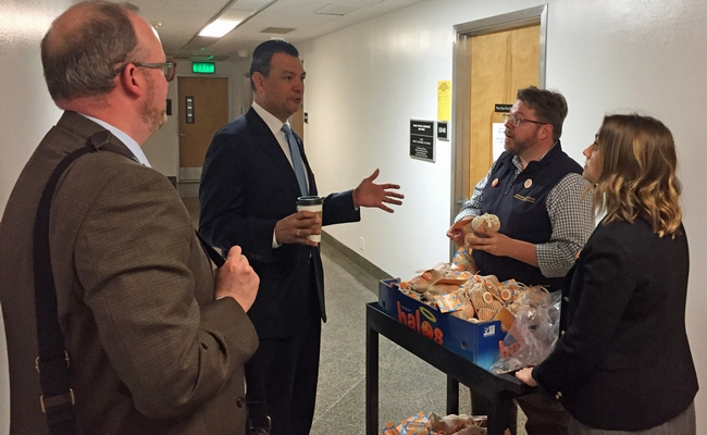 Secretary of State Alex Padilla, second from left, stopped Lucas Frerichs and Meredith Turner in the Capitol hallway to discuss mandarins.