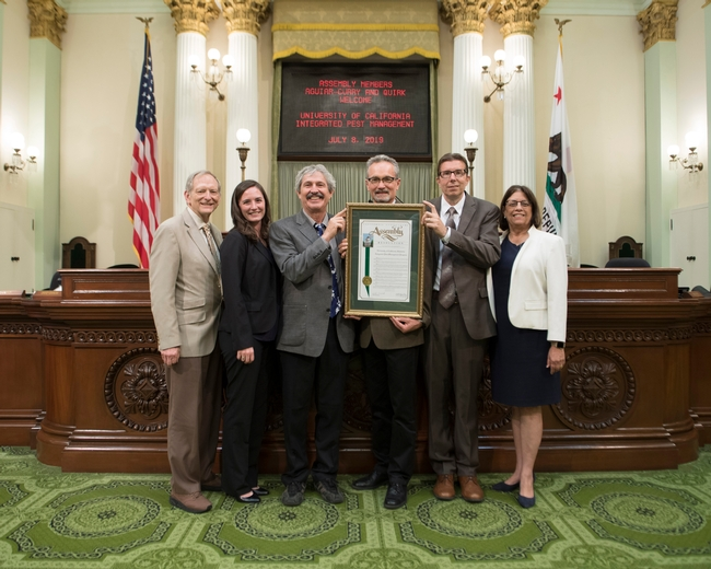 Assemblymembers Cecilia Aguiar-Curry and Bill Quirk presented Jim Farrar with a proclamation honoring UC IPM at the Capitol.
