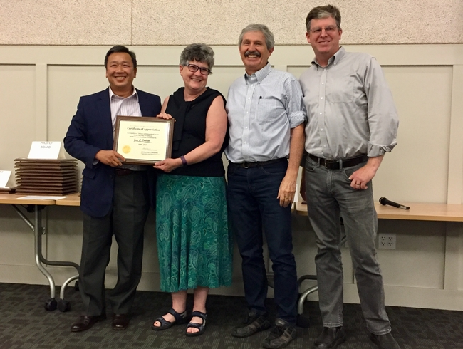 Jan Corlett, second from left, receives thanks and congratulations from Tu Tran, Mark Bell and John Fox.