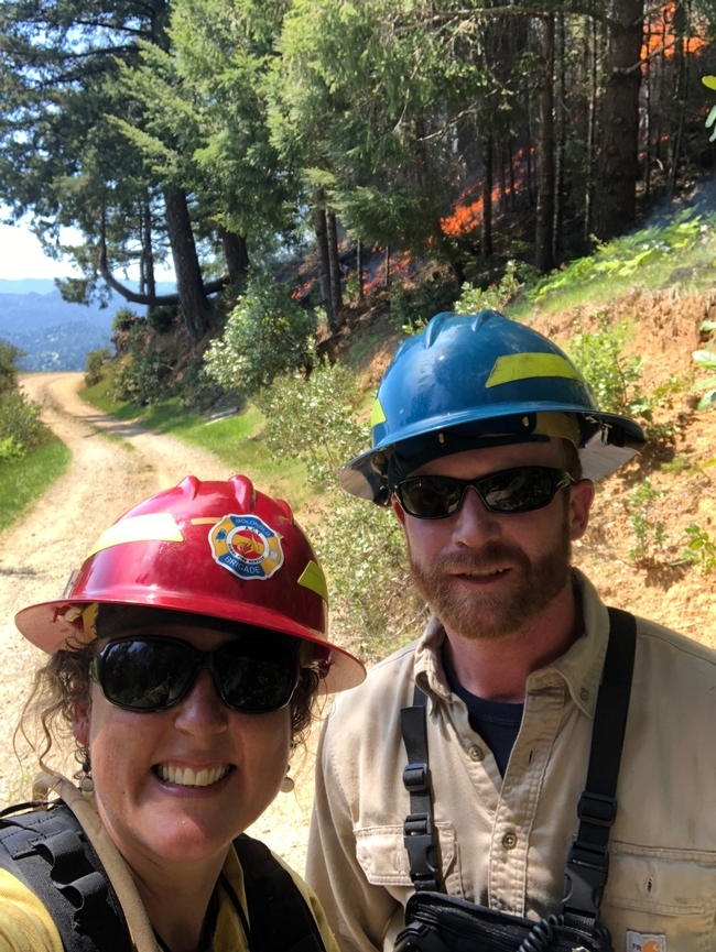 Lenya and Jeff are outdoors wearing their protective red and blue helmets as a prescribed fire burns among the trees behind them.