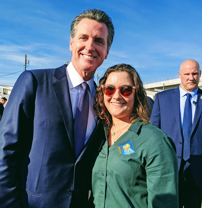 Gov. Newsom, wearing a dark suit, stands beside Katherine Uhde, who is wearing a green Master Gardener blouse.