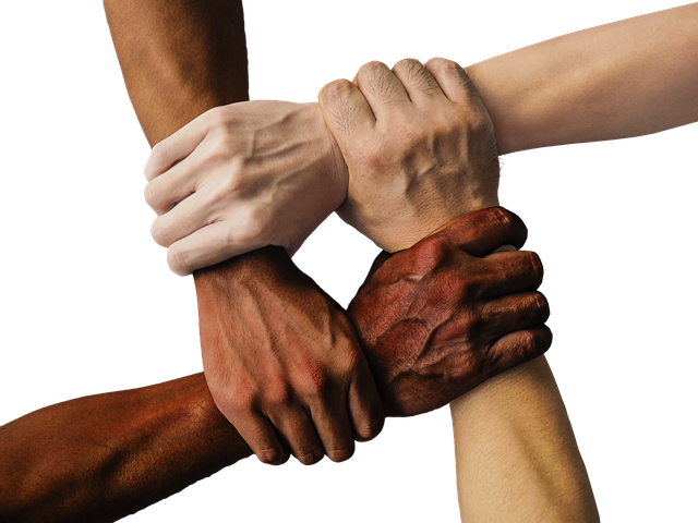 Four hands of light to dark skin color grip the wrist of another to form a closed link.