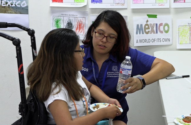 Claudia Diaz Carrasco talks with a student at an event in pre-COVID-19 times.