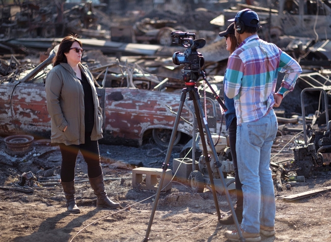 Faith Kearns stands with two film crew members beside the remains of a burned car during the Kincade Fire.