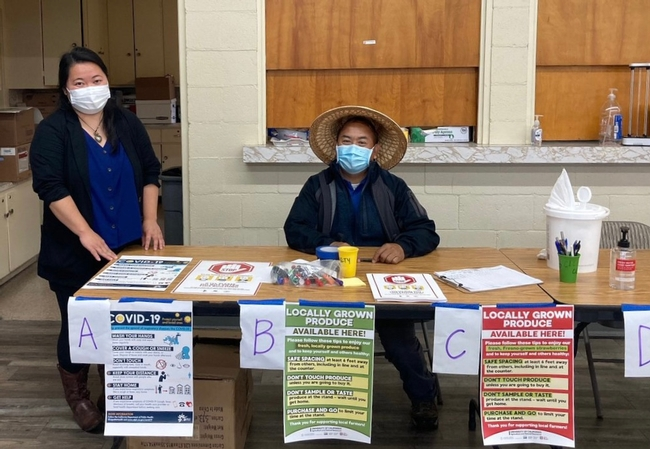 Two UCCE Hmong small farms representatives sit behind a table displaying COVID-19 signs.